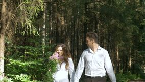 Beautiful young couple in white clothes walking in the woods. They are happy, smiling and holding hands stock footage