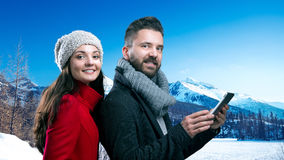 Beautiful young couple in winter clothes in winter mountains Stock Image