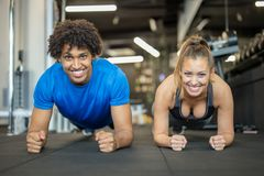 Beautiful young couple working out at the gym doing planks stock photos