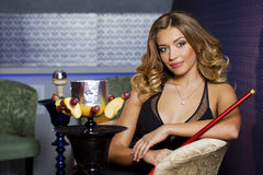 Beautiful young curly blonde woman resting in the hookah room Royalty Free Stock Images