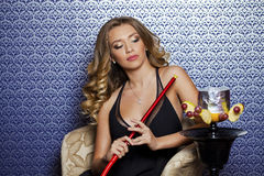 Beautiful Young Curly Blonde Woman Resting In The Hookah Room Royalty Free Stock Photography
