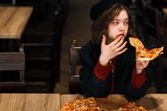 Beautiful young curly girl in black hat with piece of pizza stock images