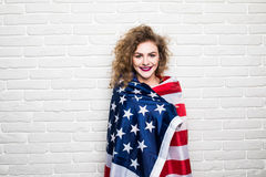 Beautiful young curly girl in casual clothes posing and smiling, standing covered with American flag against brick wall Royalty Free Stock Image