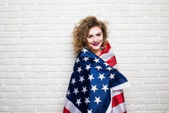 Beautiful young curly girl in casual clothes posing and smiling, standing covered with American flag against brick wall Stock Photos