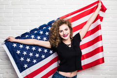 Beautiful young curly girl in casual clothes posing and smiling, standing covered with American flag against brick wall Stock Images