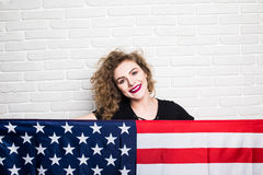 Beautiful young curly girl in casual clothes posing and smiling, standing covered with American flag against brick wall Royalty Free Stock Photos