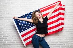 Beautiful young curly girl in casual clothes posing and smiling, standing covered with American flag against brick wall Stock Photo