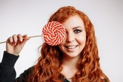 Beautiful young redhead woman holding a red white lollipop on white background. Beautiful young curly redhead surprised girl holding a red white lollipop on stock photography