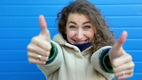 Beautiful young curly woman showing two thumb up and smiling, near blue wall
