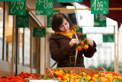 Beautiful young customer selecting tangerines Stock Photo