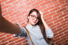 Beautiful young dark-haired girl in casual clothes and eyeglasses posing, smiling and making selfie Royalty Free Stock Photography
