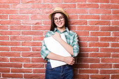 Beautiful young dark-haired girl in casual clothes, hat and eyeglasses posing Royalty Free Stock Photography