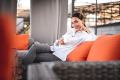 Pretty young lady smiling to the camera while sitting with coffee stock images