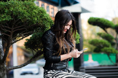 Beautiful young dark-haired woman is texting on her smartphone while sitting the bench in city park Royalty Free Stock Image