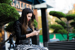 Beautiful young dark-haired woman is texting on her smartphone while sitting the bench in city park Stock Photography