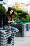 Beautiful young dark-haired woman is texting on her smartphone while sitting the bench in city park Stock Photo