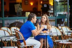 Beautiful young dating couple in Parisian cafe Stock Photos