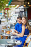 Beautiful young dating couple in Parisian cafe Stock Images