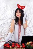 DJ woman New Year Santa costume headphones silver background party girl red horns christmas decorations brunette white dress stock image
