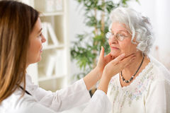 Beautiful young doctor examining senior woman lymph glands Royalty Free Stock Images