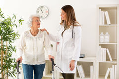 Beautiful young doctor helping senior woman walking with a walke Royalty Free Stock Image