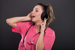 Beautiful young doctor singing listening to headphones Stock Images