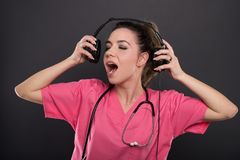 Beautiful young doctor singing listening to headphones Royalty Free Stock Photos