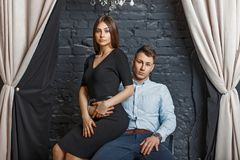 Beautiful young elegant couple in stylish clothes sitting royalty free stock image