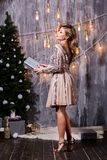 Beautiful young elegant woman in Golden dress posing over grey background with glitter ribbons christmas balls holding royalty free stock photography