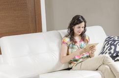 Beautiful young elegant woman sitting in sofa using tablet. Royalty Free Stock Photo
