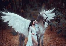 Beautiful, young elf, walking with a unicorn. She is wearing an incredible light, white dress. Art hotography. Beautiful, young elf, walking with a unicorn. She Stock Photo