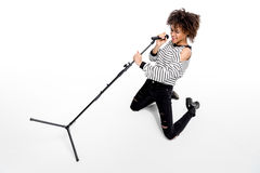 Beautiful young emotional heavy metal singer with microphone singing Royalty Free Stock Photography
