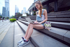 Beautiful young European girl sitting with a laptop on the steps of the city in the background. Stock Image