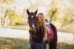 Woman stands next to a black horse and strokes her, in an autumn park. stock photo