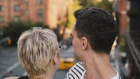 Beautiful young European woman and Hispanic man standing and hugging on a bridge talking, enjoying city scenery close-up. Relaxed smiling multiethnic couple stock video