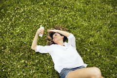 Beautiful, young, European woman lays down on grass and looks at at camera Royalty Free Stock Photos