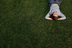 Beautiful young european woman lays down on grass and rests Royalty Free Stock Photos