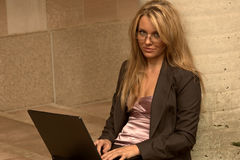 Beautiful young executive. Beautiful young business woman typing on a laptop Royalty Free Stock Photography