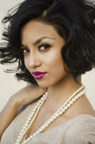 Beautiful young exotic woman. Beautiful young elegant exotic woman with short hair wearing pearls Royalty Free Stock Image