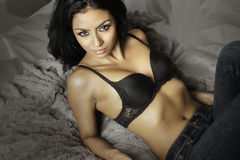 Beautiful young exotic woman holding gun. Beautiful young exotic woman wearing black bra and denim jeans Stock Images