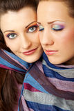 Beautiful young faces. Close-up of two  young female faces with colourful makeup Royalty Free Stock Photography