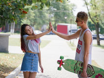 A young girl giving five her cute boyfriend with a longboard on a blurred park background. Relationship and love concept stock photos