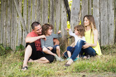 Beautiful young family against old wooden fence. Summer nature. stock photo