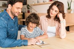 Beautiful young family in cafe looking. At paycheck royalty free stock photos