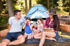 Beautiful young family with daughters camping in forest. Royalty Free Stock Images