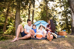 Beautiful young family with daughters camping in forest. Stock Image
