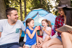 Beautiful young family with daughters camping in forest. Royalty Free Stock Photo