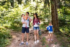 Beautiful young family with daughters going camping in forest. Royalty Free Stock Photo