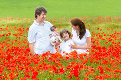 Beautiful young family enjoying in red flower field Royalty Free Stock Photos
