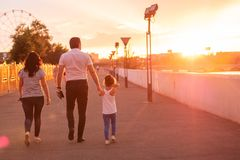 Beautiful young family of four walking stock image